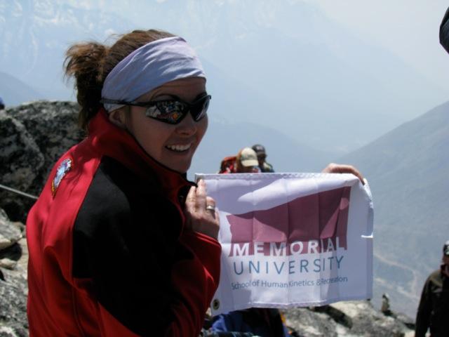 Jacinta holding the HKR flag atop Nagarsang Peak in Nepal
