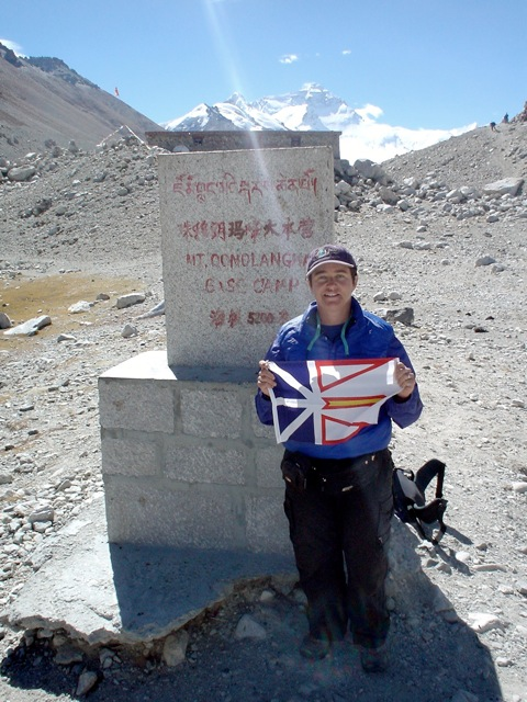 TA holding the Newfoundland flag at Mount Everest Base Camp on the Tibetan side of the mountain.