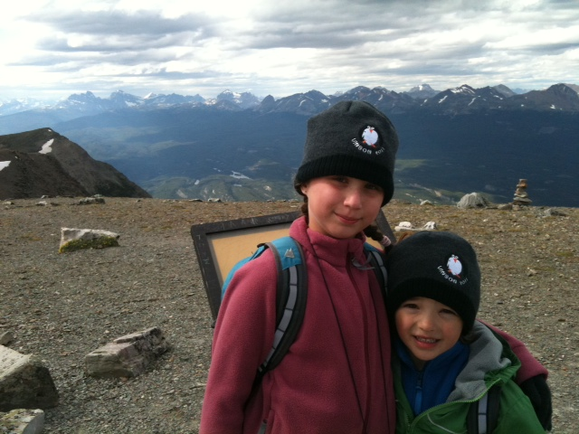 Rayne and Xander pose in their Mount Vinson Penguin toques on the summit of Mount Whistler