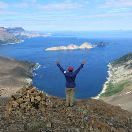 TA standing with arms raised overlooking the Labrador Sea from a high viewpoint