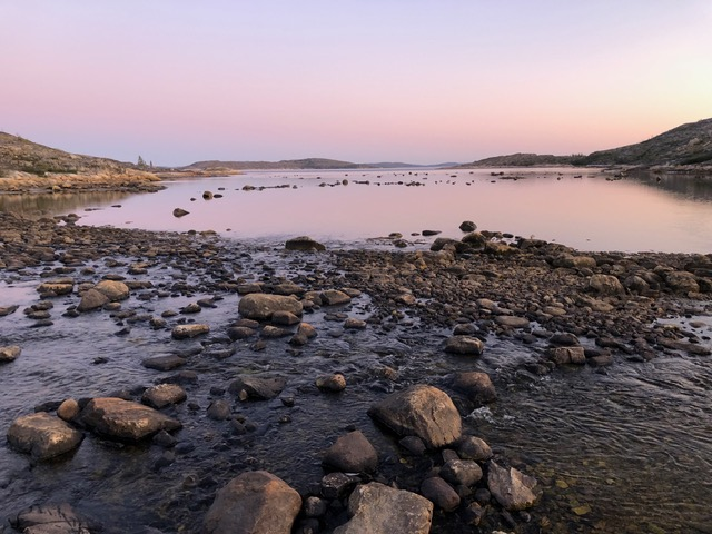 Still waters in early morning light with boulders sticking out at low tide