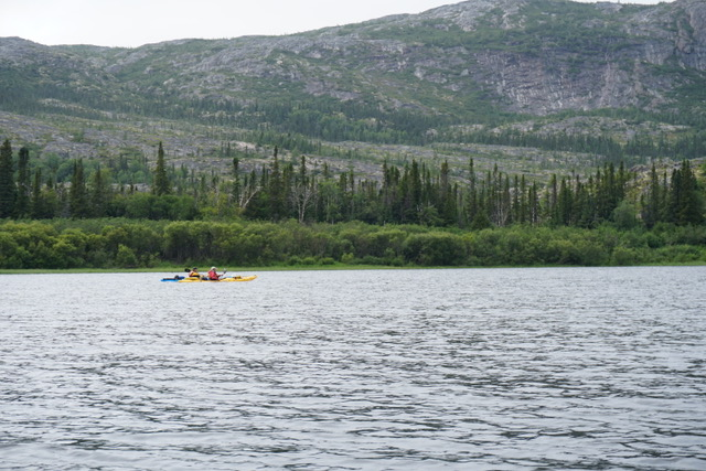 Two kayakers paddling with a rocky mountain in the background