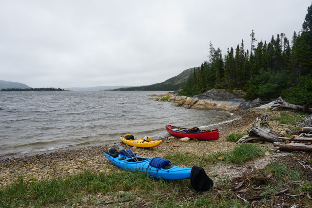 Canoe and kayaks on the beach with waves on the sea behind them
