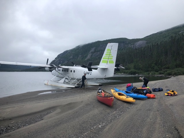 A floatplane parked at a beat with canoes and kayaks on the beach