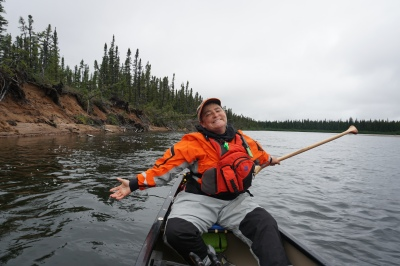 TA smiling with arms wide open on the Adlatok River in Labrador